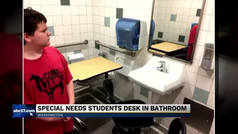 An autistic student's desk moved to a bathroom stall
