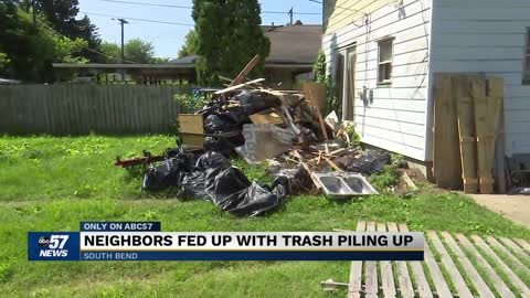 Neighbors fed up with 10 ft trash pile-up in neighbors yard