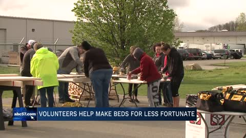Volunteers build beds for children in need
