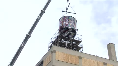 Mosaic sculpture gets lifted onto Coakley Brothers building
