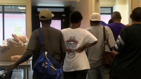 """It's just too hot:"" Dozens line up at one of few cooling sites open on Sunday"