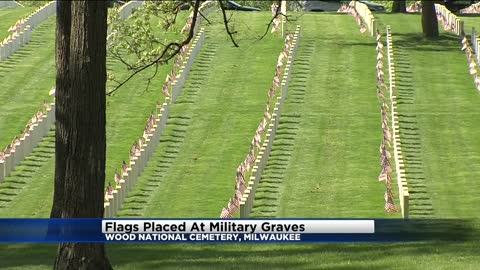 Volunteers place flags at Wood National Cemetery ahead of Memorial Day