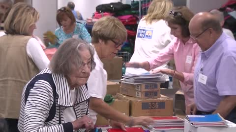 Volunteers help stuff backpacks with school supplies